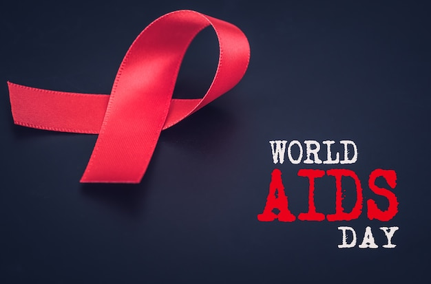 Closeup red ribbon awareness on black background for world aids day campaign Premium Photo