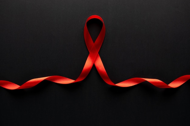 Closeup red ribbon awareness on black paper for world aids day campaign. Premium Photo