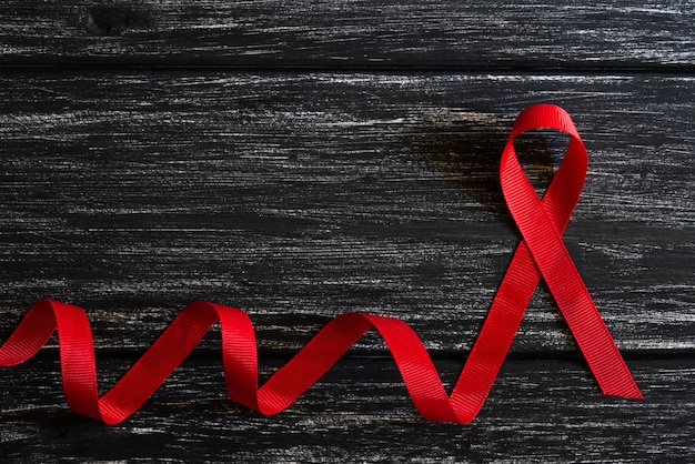Closeup red ribbon awareness on black wooden table background  for world aids day campaign Premium Photo