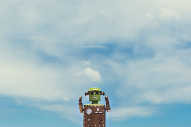 Closeup of robot toy with cloudy blue sky scenic Free Photo