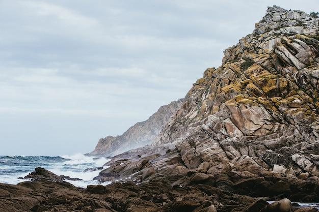Primo piano delle rocce circondate dal mare sotto un cielo nuvoloso durante il giorno Foto Gratuite