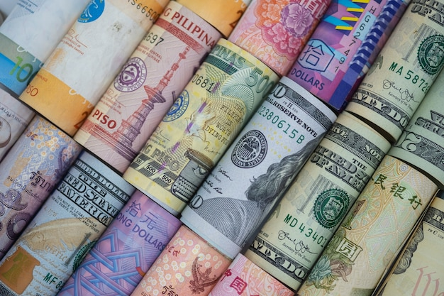 Closeup rolled of variety banknote around the world. exchange rate and forex investment concept Premium Photo