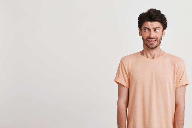 Primo piano del giovane triste insoddisfatto con setola indossa maglietta color pesca si sente dispiaciuto e aggrottando la fronte il suo volto isolato su bianco Foto Gratuite