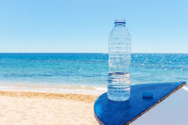 Closeup of the sea view and plastic bottle with water on table Premium Photo