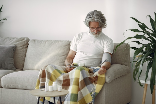 Primo piano del maschio anziano 70-75 anni che misura la pressione. uomo per misurare la sua pressione sanguigna. salute e cura. Foto Gratuite
