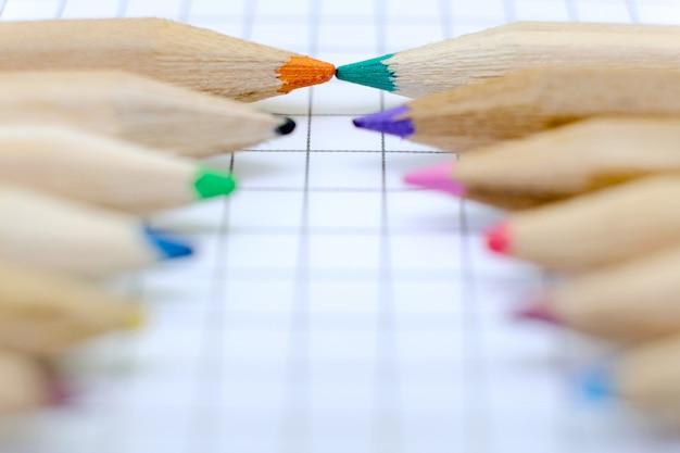 Комплект крупного плана красочных карандашей на checkered бумажном листе тетради для чертежа. обратно в школу концепции. Premium Фотографии