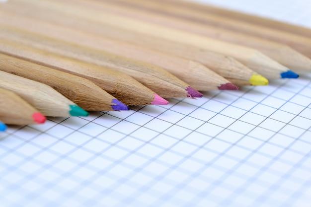 Макрофотография набор разноцветных карандашей на клетчатый лист бумаги тетради для рисования. обратно в школу концепции. Premium Фотографии