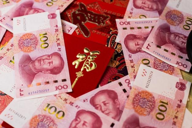 Colpo del primo piano di 100 yuan cinesi (cny) banconote e busta rossa tradizionale cinese Foto Gratuite