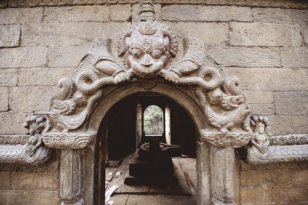 Colpo del primo piano di una porta ad arco con scolpire in un tempio indù in nepal Foto Gratuite