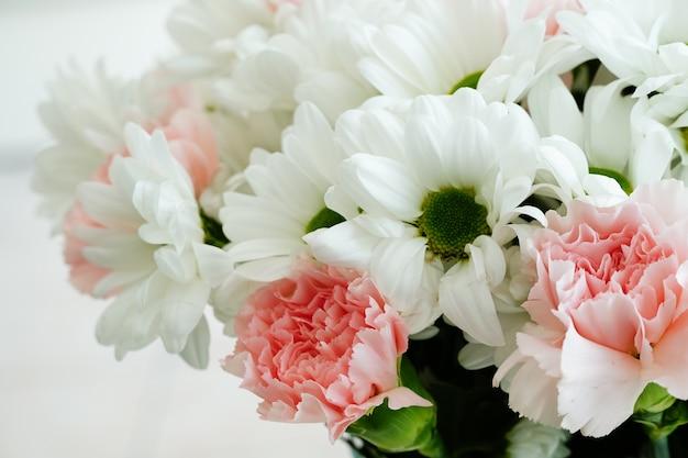 Colpo del primo piano di un bellissimo bouquet con fiori colorati e margherite del transvaal sotto le luci Foto Gratuite