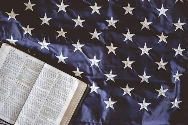 Colpo del primo piano della bibbia aperta nelle pagine messe sulla bandiera americana - perfetto per il concetto di preghiera Foto Gratuite