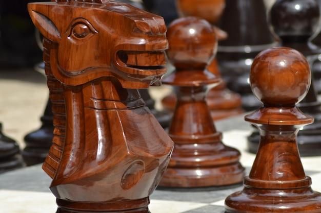 Colpo del primo piano di grandi figure di scacchi all'aperto in legno con uno sfondo sfocato Foto Gratuite