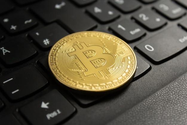 Colpo del primo piano di un bitcoin messo sulla tastiera di un computer nero Foto Gratuite