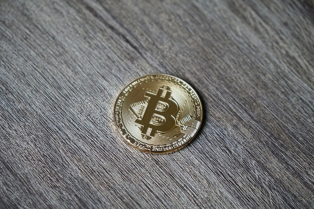 Closeup shot of a bitcoin on a wooden table Free Photo