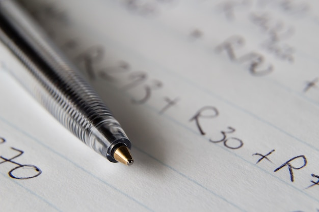 Closeup shot of a black pen on a piece of paper with some numbers and codes written on it Free Photo