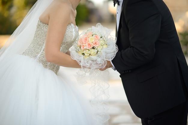 Colpo del primo piano di una sposa e uno sposo che si baciano mentre si tiene il bellissimo bouquet Foto Gratuite