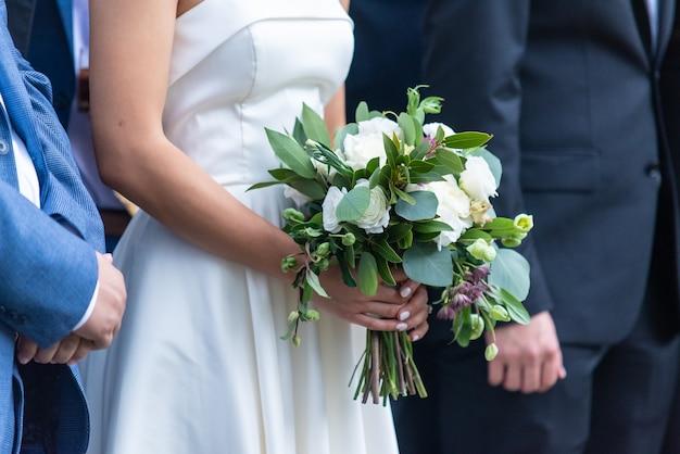 Colpo del primo piano di una sposa che tiene il suo bellissimo bouquet in piedi presso l'altare Foto Gratuite