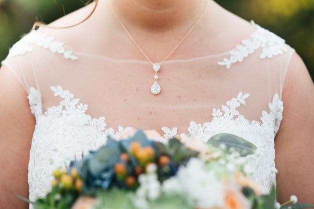 Colpo del primo piano della sposa in un abito da sposa che tiene il bouquet Foto Gratuite