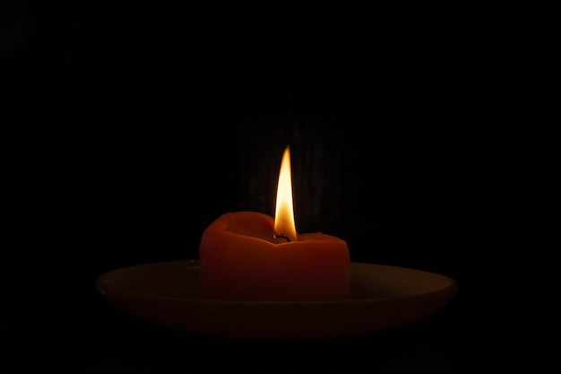 Closeup shot of a burning candle in the dark Free Photo