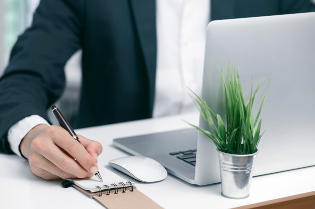 Closeup shot businessman using pen writing on notebook while working with laptop at modern office. Premium Photo