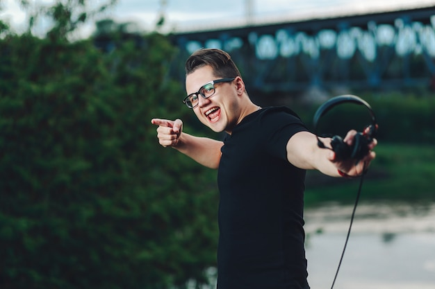 Closeup shot of casual young man in hipster glasses with headphones on the summer nature background Premium Photo