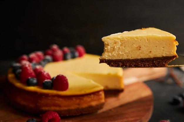 Colpo del primo piano di una fetta di torta di formaggio con la torta con frutti di bosco in cima Foto Gratuite