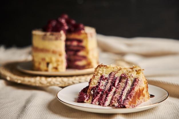 Colpo del primo piano di una fetta della torta della ciliegia sulla zolla bianca Foto Gratuite