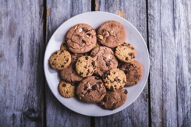 Closeup shot of chocolate chip cookies in a white plate on a wooden surface Free Photo