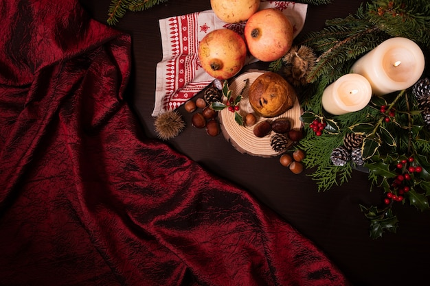 Closeup shot of a christmas decoration with candles pine branch cones fruits and panettone Free Photo
