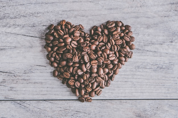 Closeup shot of coffee beans in shape of a heart on a gray wooden background Free Photo
