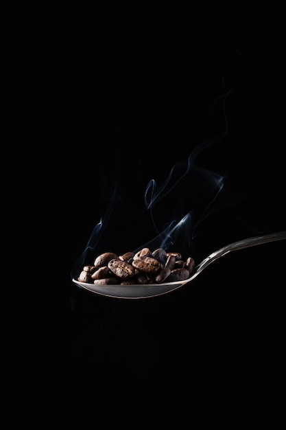 Closeup shot of coffee beans in a spoon with smoke on dark Free Photo