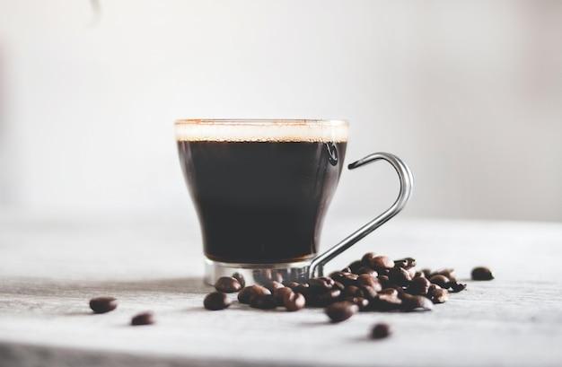 Colpo del primo piano di una tazza di caffè nero sul tavolo con chicchi tostati sotto le luci Foto Gratuite