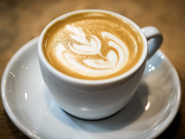 Closeup shot of a cup of cappuccino with beautiful coffee art Free Photo