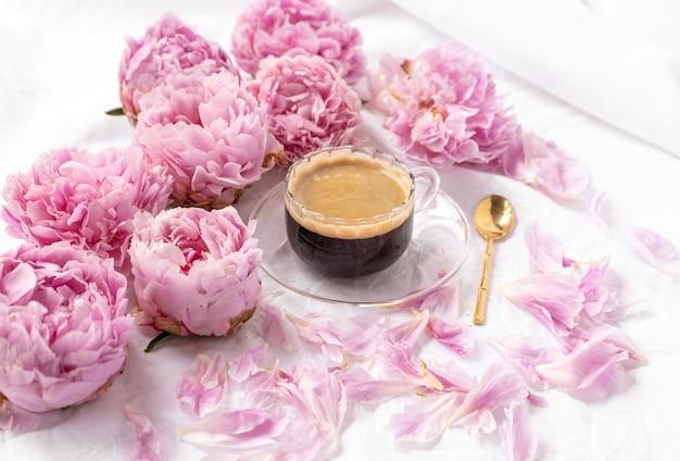 Colpo del primo piano di una tazza di caffè istantaneo su un piattino sul tavolo con peonie rosa su di esso Foto Gratuite