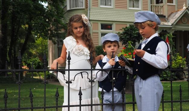 Colpo del primo piano di una bambina carina e due ragazzi in costumi identici in piedi dietro il recinto Foto Gratuite