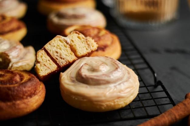Closeup colpo di deliziosi panini alla cannella con glassa bianca su una tavola nera Foto Gratuite