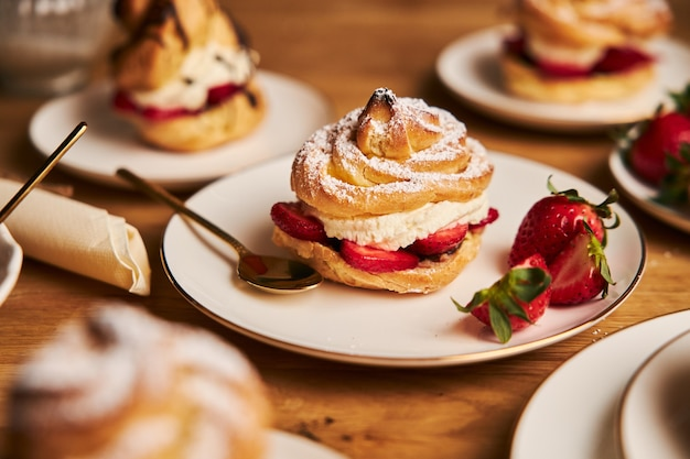 Closeup shot of delicious cream puff with strawberries on a wooden table Free Photo