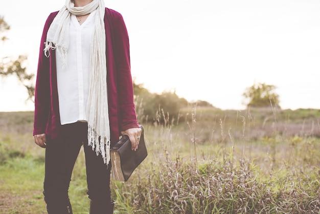 Colpo del primo piano della donna in piedi in un campo erboso mentre si tiene la bibbia con sfondo sfocato Foto Gratuite