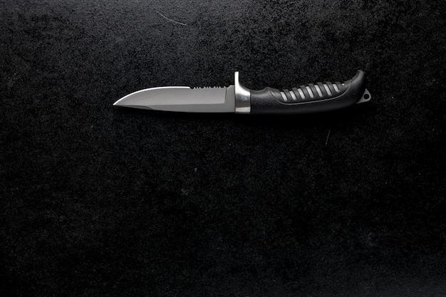 Closeup shot of a fixed sharp knife on a black table Free Photo