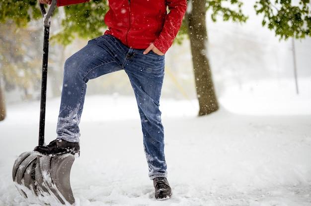 雪原に立っている間雪のシャベルに彼の足を持つ男性のクローズアップショット 無料写真