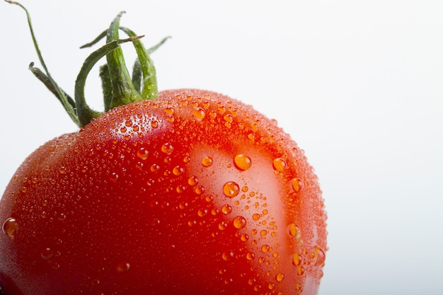 Closeup shot of a fresh tomato with drops of water on it isolated on a white background Free Photo