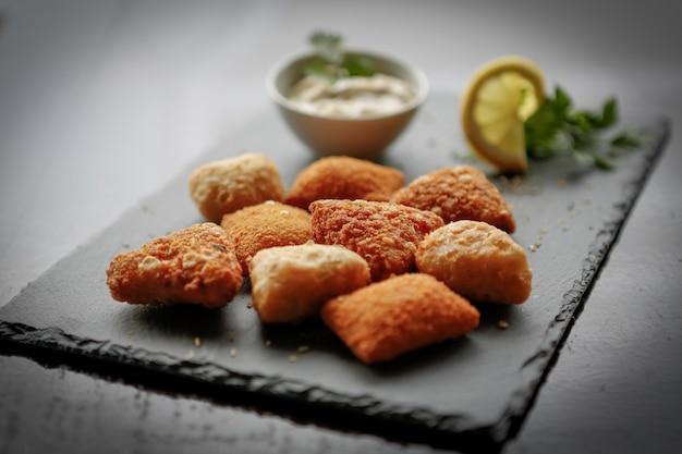 Closeup shot of fried potato cheese balls or croquettes over dark stone board Free Photo