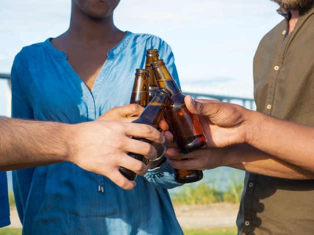 Closeup shot of friends clinking beer bottles. group of young people relaxing after work. celebration concept Free Photo