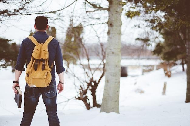 Макрофотография выстрел из-за мужчины носить желтый рюкзак и держа библию Бесплатные Фотографии