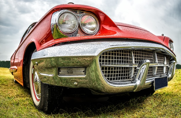 Closeup shot of the front part of a red car parked on a green field Free Photo