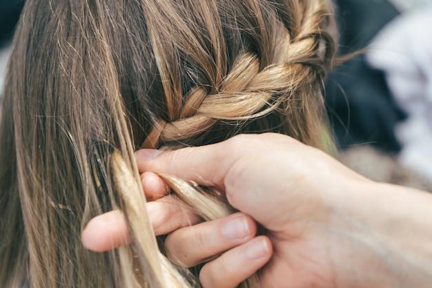 Closeup shot of a girl getting her braids done Free Photo
