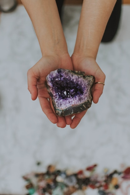 Colpo del primo piano di una ragazza che tiene una roccia multicolore nelle sue mani su una superficie bianca Foto Gratuite