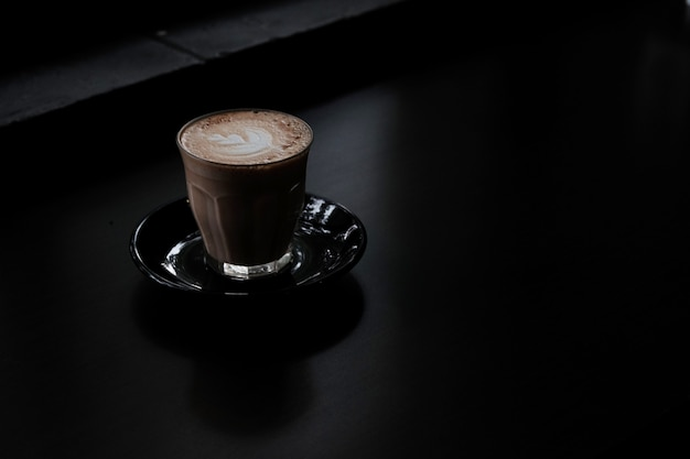 Closeup shot of a glass of coffee on a black surface Free Photo