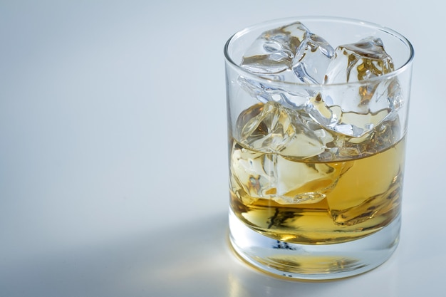 Closeup shot of a glass full of ice and some whiskey isolated on a white background Free Photo