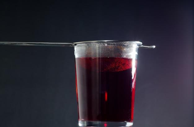 Colpo del primo piano di un bicchiere di tè rosso su oscurità Foto Gratuite